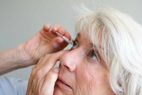 A woman applying drops to her eye.