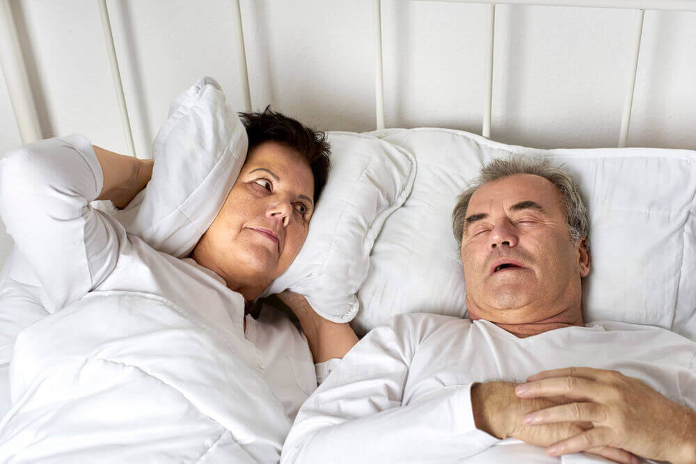 A man snoring in bed while his wife covers her ears with a pillow.