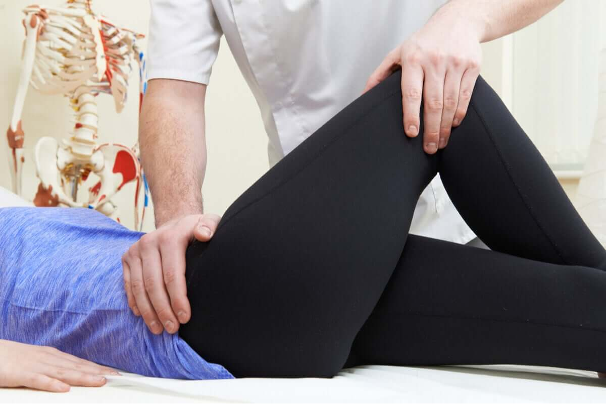 A physical therapist performing hip exercises on a patient.