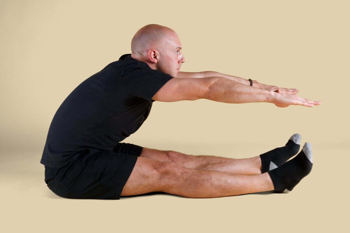 A man doing a Pilates roll up.