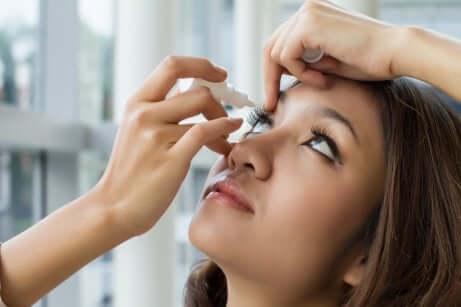 A woman using eye drops.