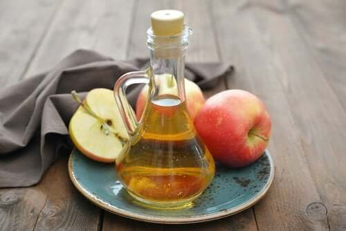 Apple cider vinegar in a jar and fresh apples on a plate.