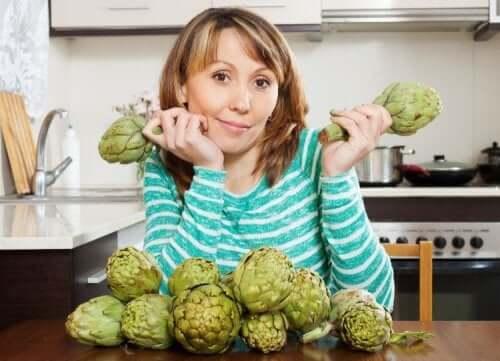 A woman holding artichokes.