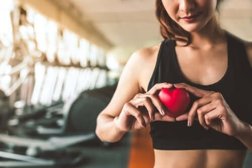 A woman at a gym holding a plastic heart in front of her chest.