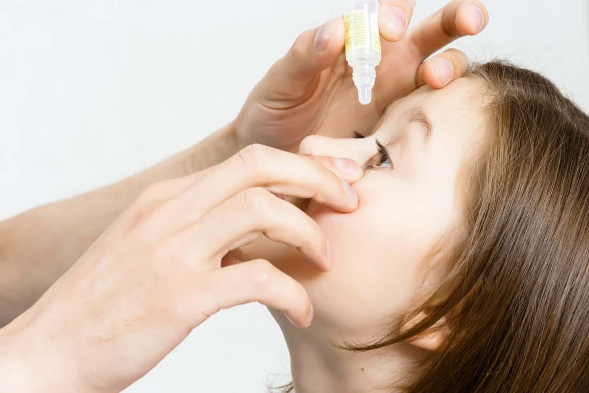 Someone putting eye drops in a child´s eyes.