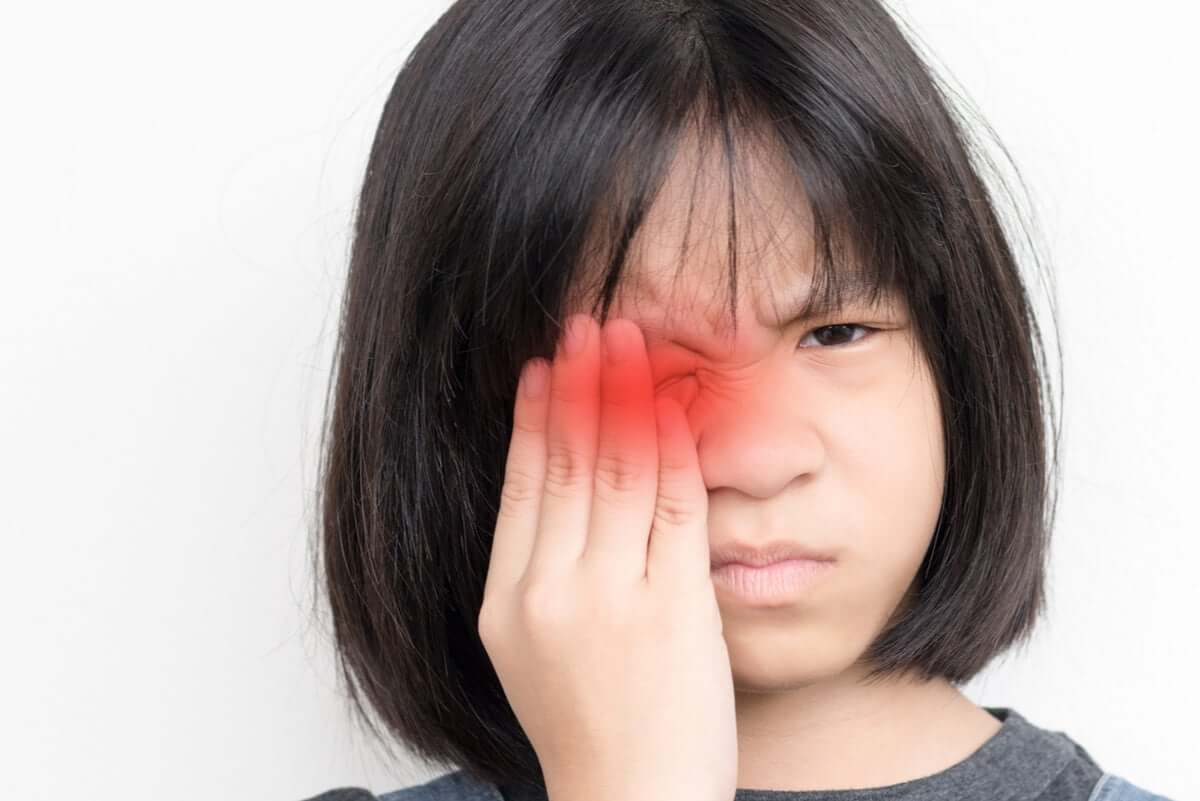 A chidl suffering from eye irritation.