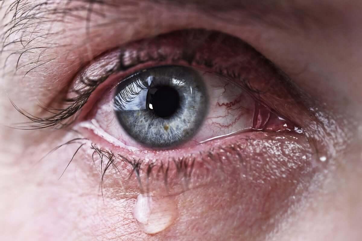 An eye with a tear drop falling down.