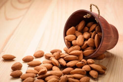 A bowl of almonds spilling out on a table.