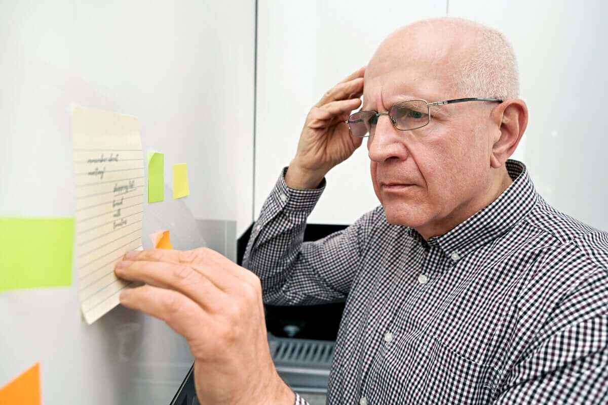 An elderly man looking at a list with a confused expression.