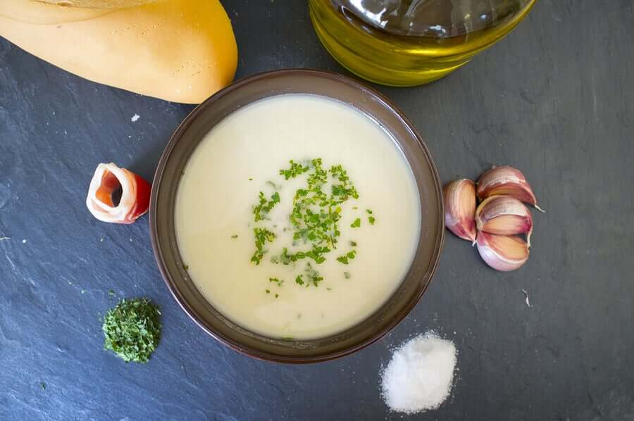A bowl of cream of almond soup surrounded by ham, garlic, oild cread, and salt.