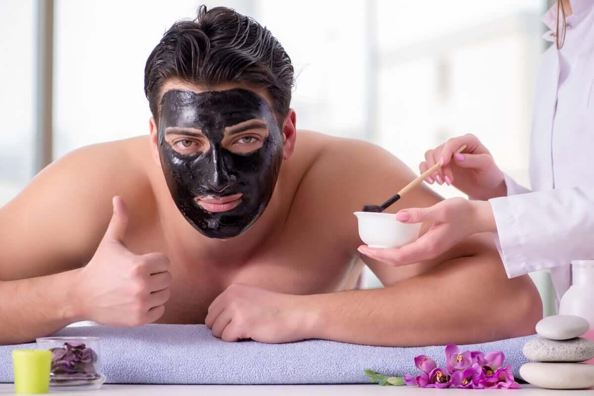 A man using a charcoal facial mask.