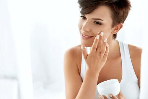 A woman applying moisturizer to her face.