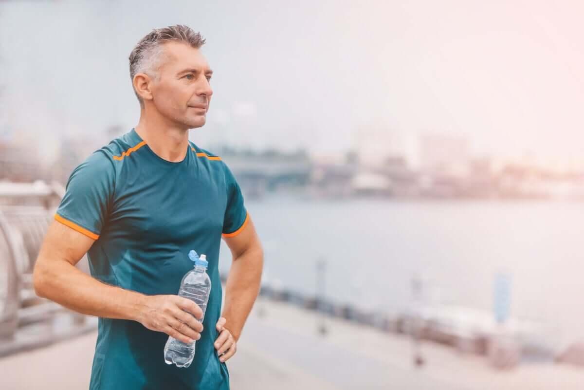 An older man drinking water after a run.