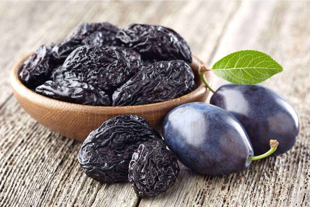 A bowl of prunes and two fresh plums.