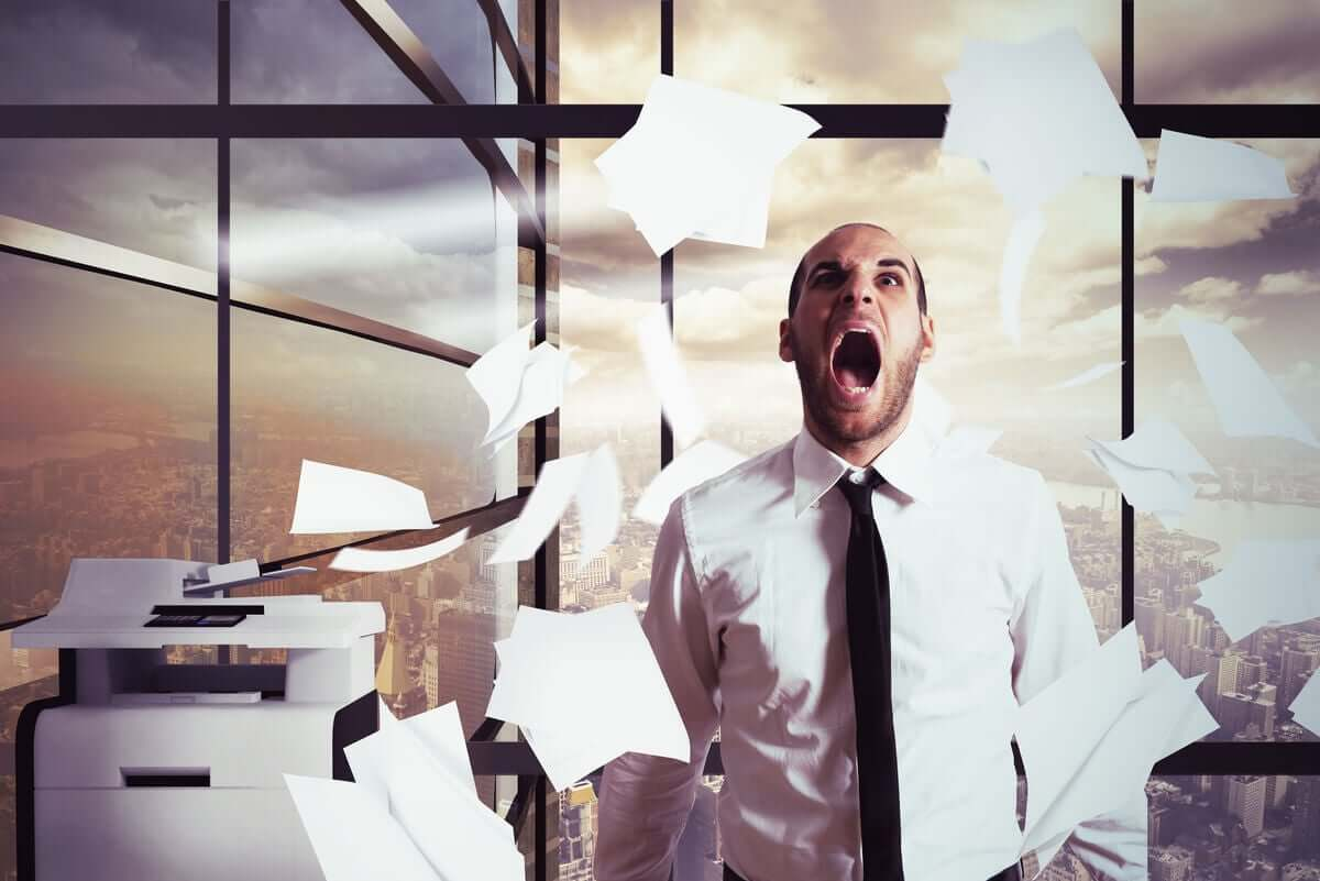 A man having a nervous breakdown at work, throwing papers in the air.