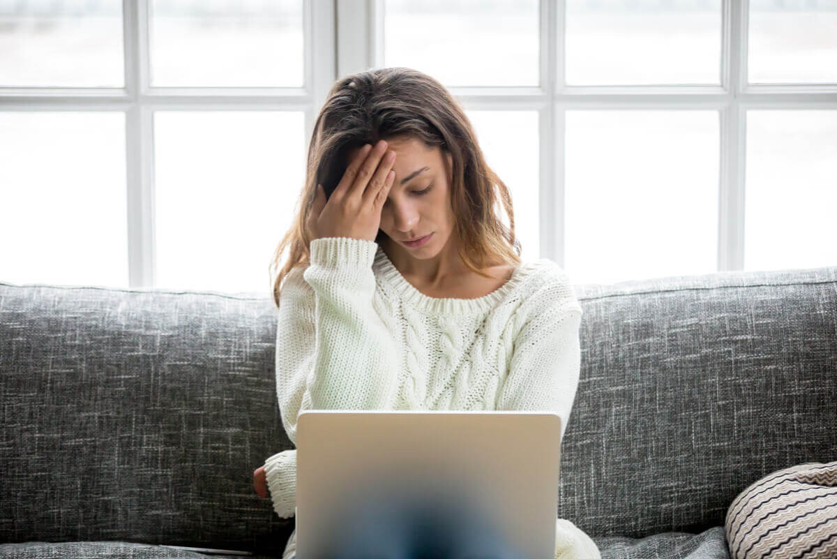 A woman experiencing stress while working on her laptop on the couch.