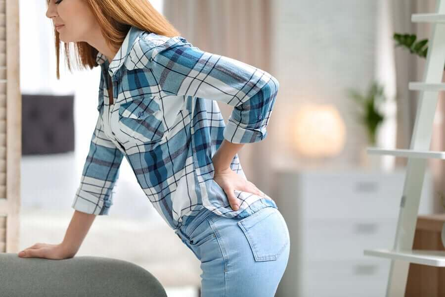 A woman bending over with her hand on her lower back.