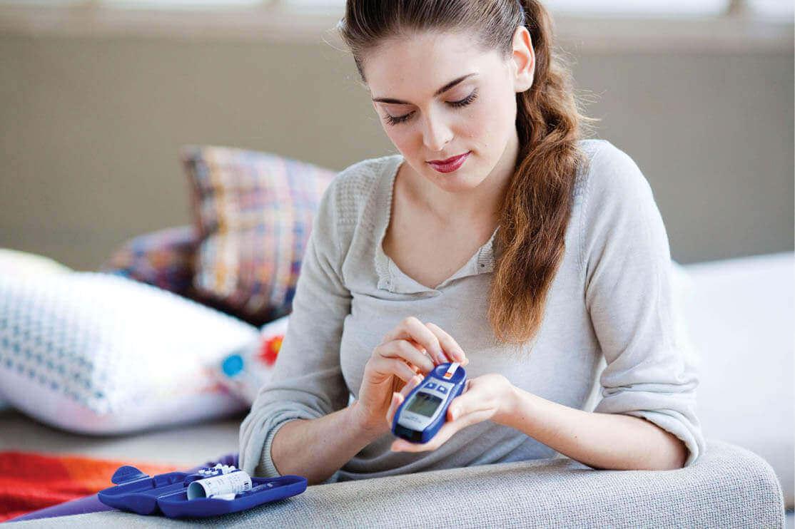 A woman testing her blood sugar.