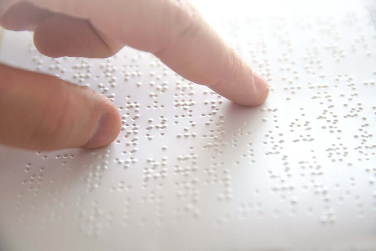 A blind person reading with Braille.