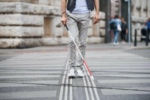 A blind person walking with a cane.