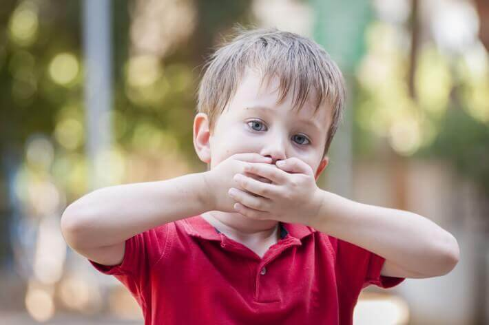 A child covering his mouth with both hands.