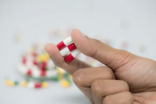 A person holding three manidipine capsules.
