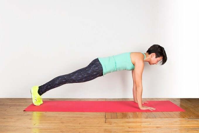 A woman doing a plank on a yoga mat.