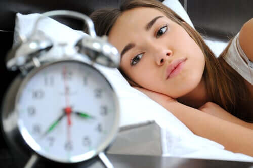 A woman looking at the alarm clock.