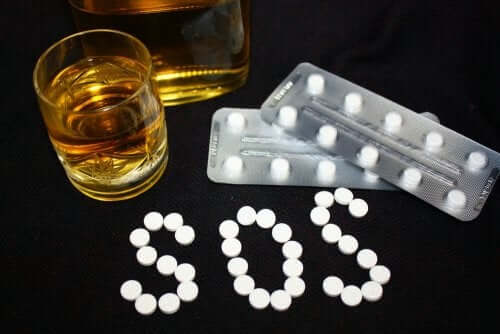 A glas with an alcoholic beverage next to blister packs of medication, and the letters S.O.S. written with pills.