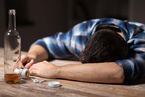A man passed out in front of a bottle of alcohol and a pill bottle.