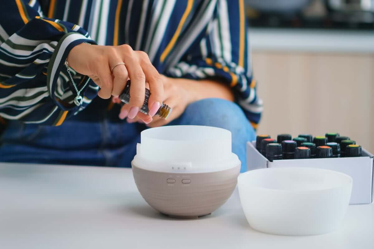 A woman pouring essential oils into an aromatherapy diffuser.