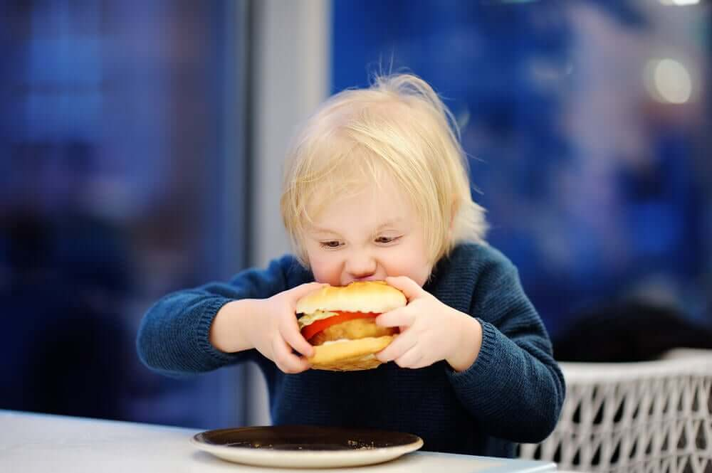 A toddler biting into a fried chicken sandwich.