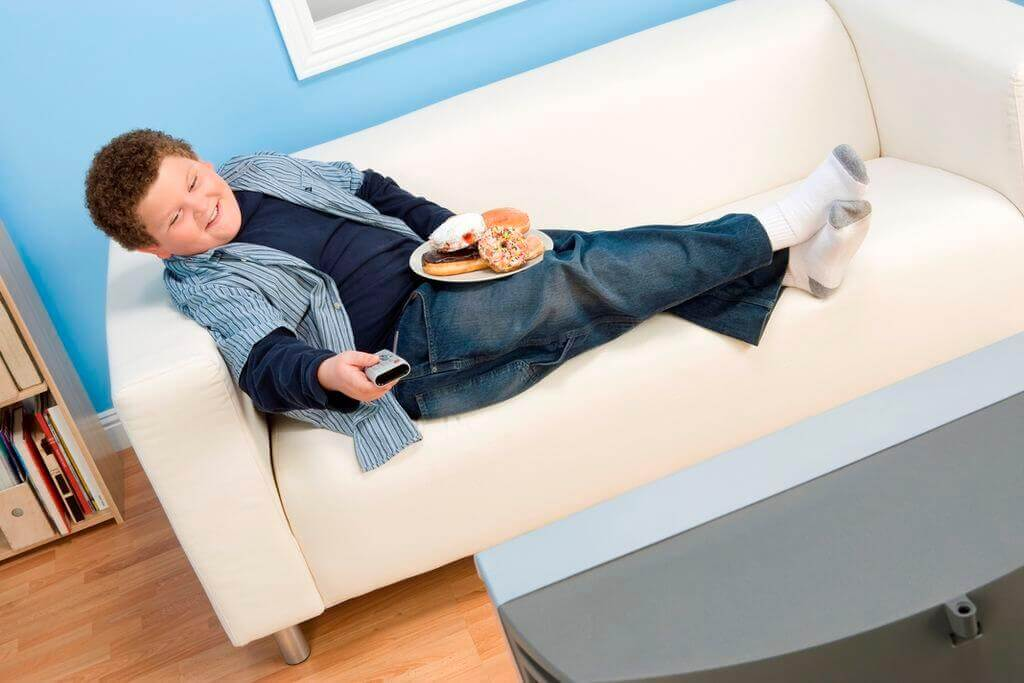 An overweight child eating donuts while sitting on the couch and watching TV.