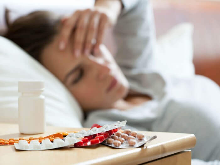Various blister packs of pills on a night stand, with a woman laying in bed looking distressed in the background.