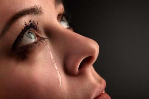 A woman looking upward with a tear falling down her cheek.