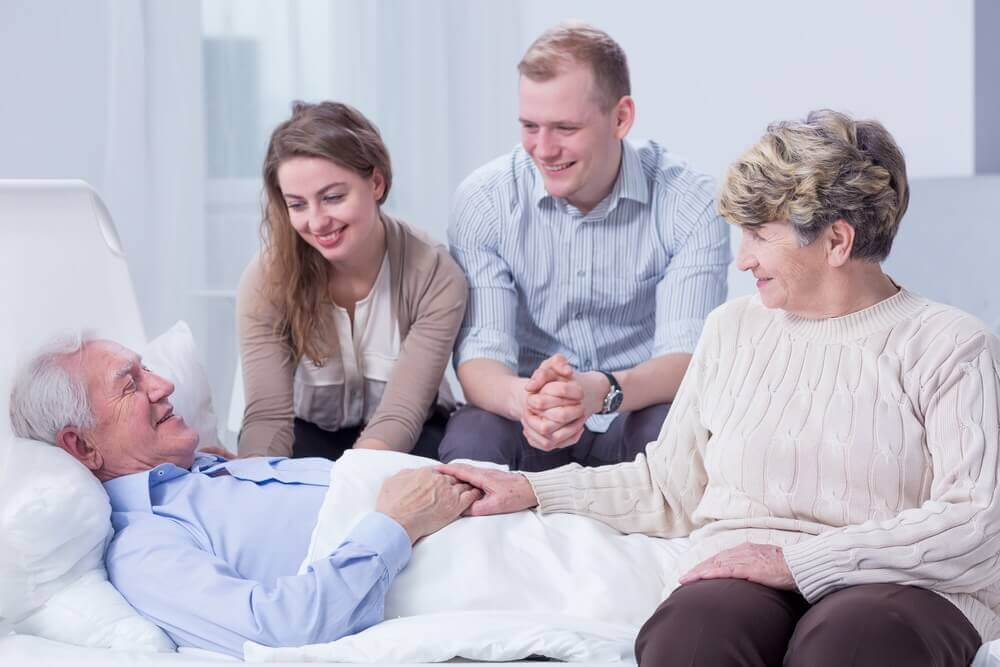 A family visiting a family member with Alzheimers that's lying in bed.
