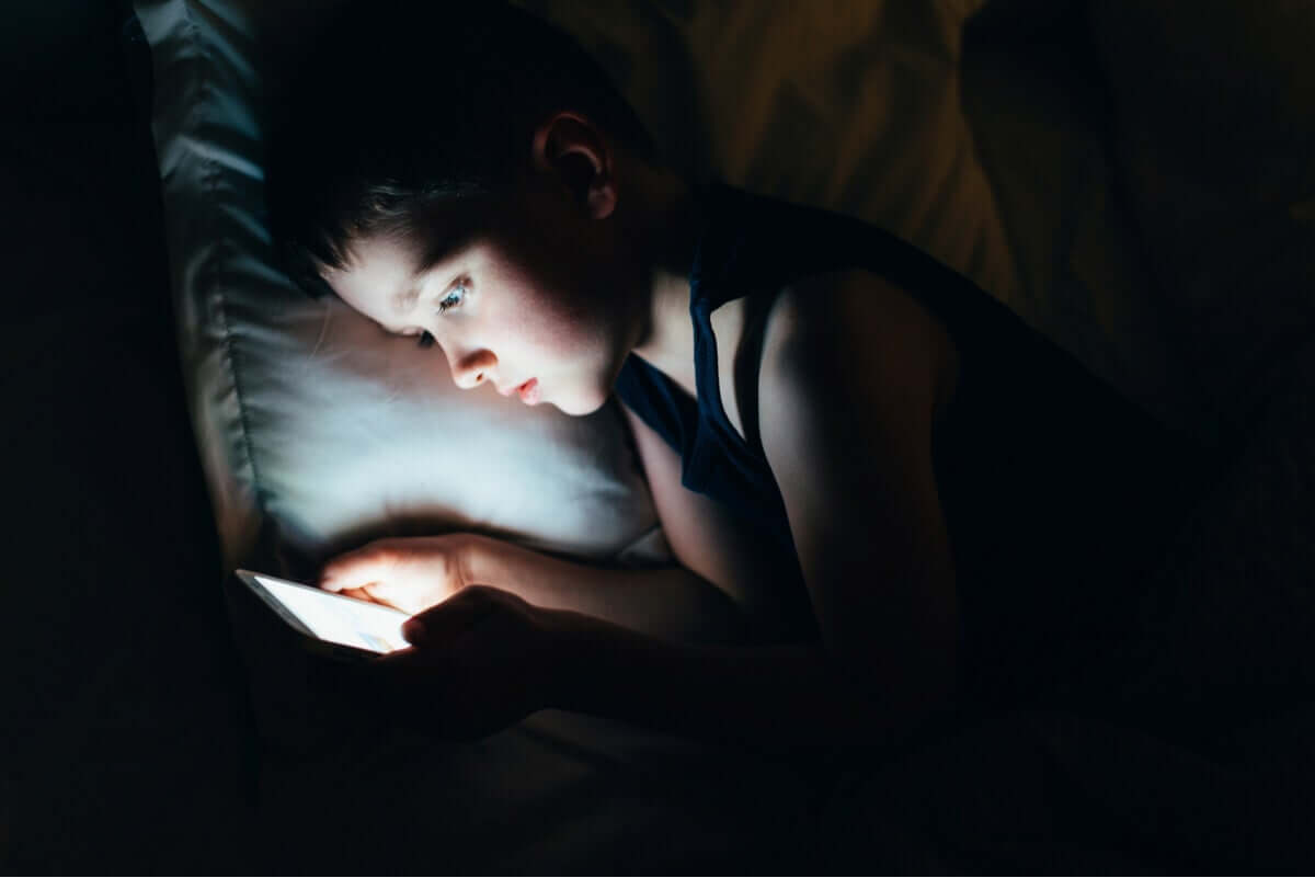 A young child looking at a tablet in bed in the dark.