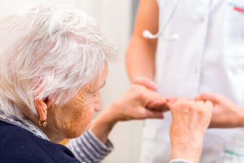 Elderly woman holding hands.