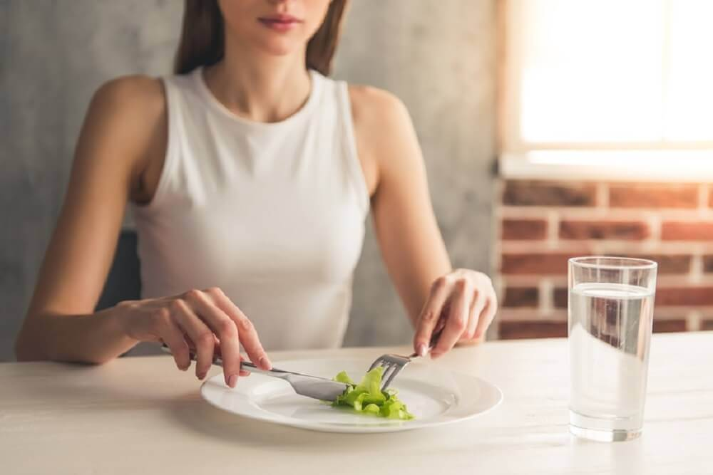 A woman eating a small portion of lettuce.