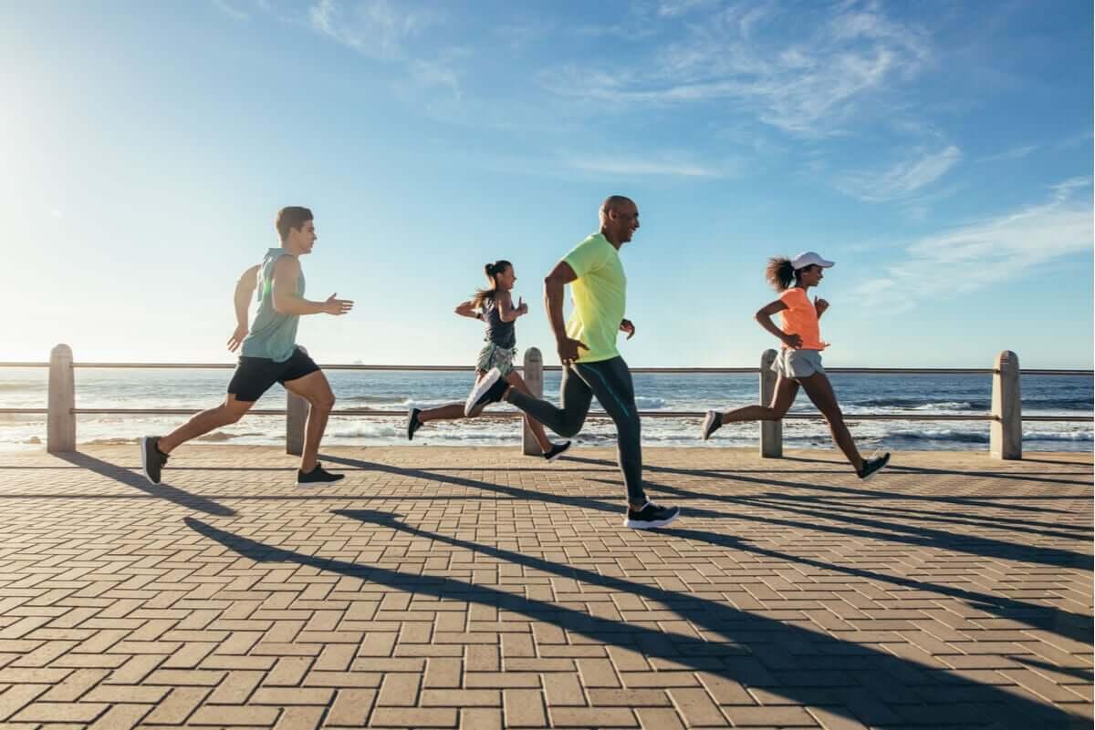 A group of runners running along the beach.