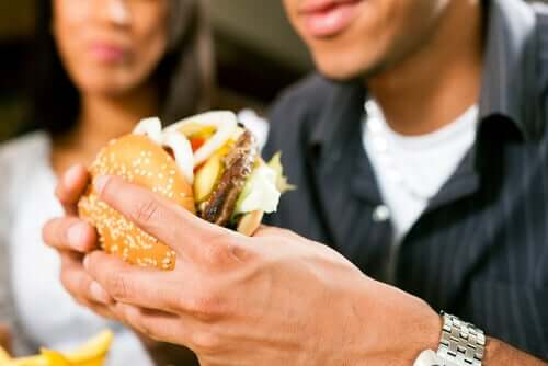 A man eating a double hamburter loaded with condiments as a woman watches in the background.