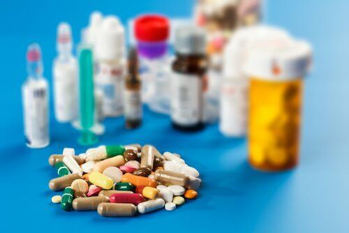 A pile of pills in front of a variety of pill bottles.