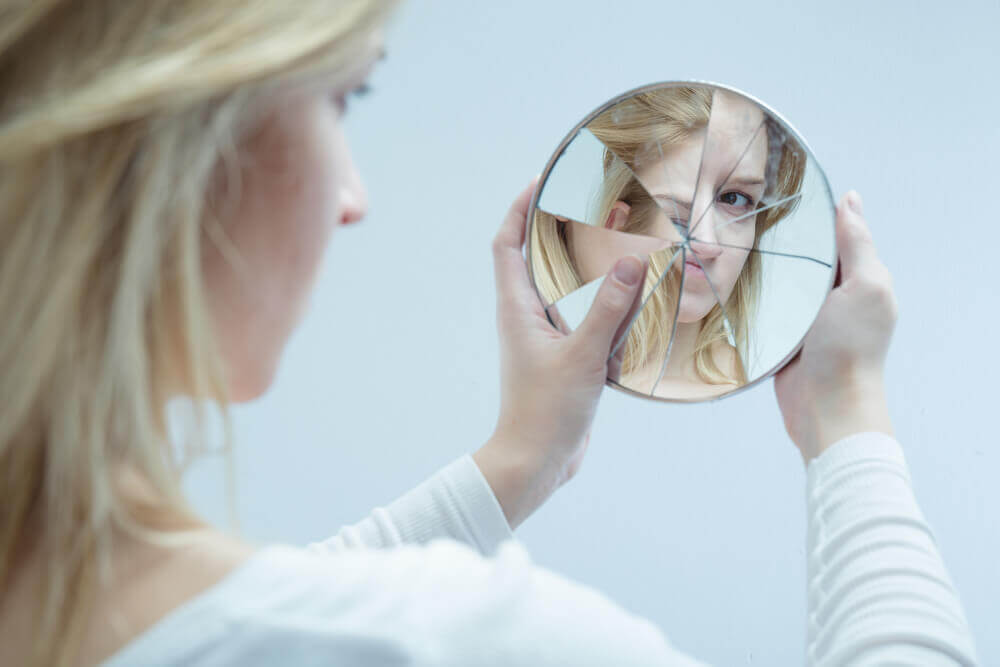 A woman looking at herself in a shattered mirror, which projects a distorted image of her face.