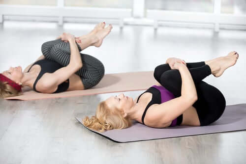 Two women stretching on yoga mats.