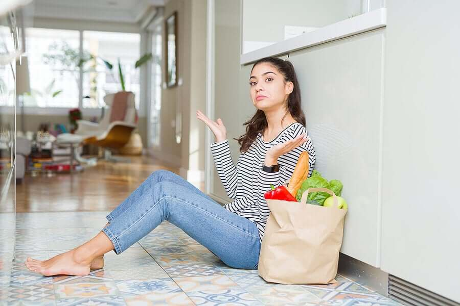 A woman sitting on the floor throwing her hands in the air, with a paper bag full of produce next to her.