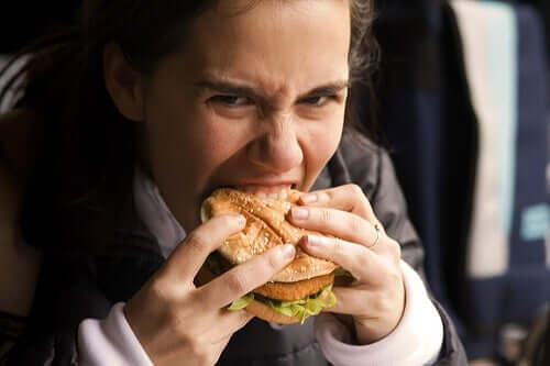 A woman biting eagerly into a sandwich.