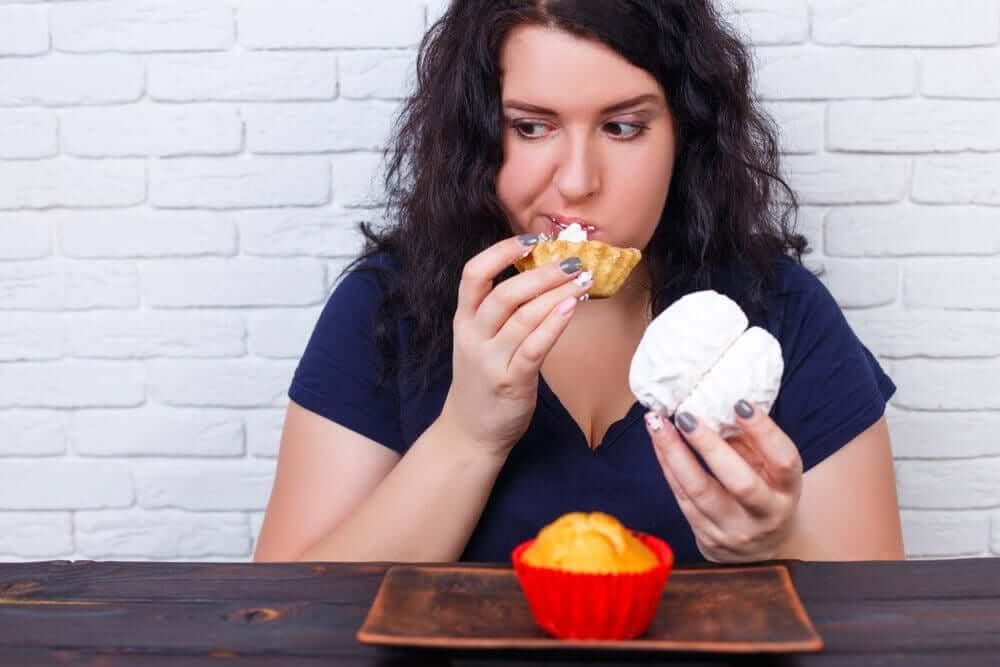 A woman with a different pastry in each hand and a cupcake on the table in front of her.