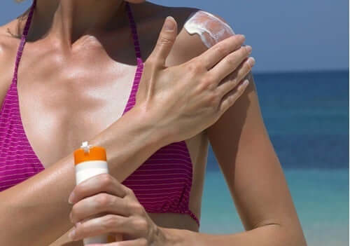 A woman is enjoying a day on the beach and applying sunscreen.