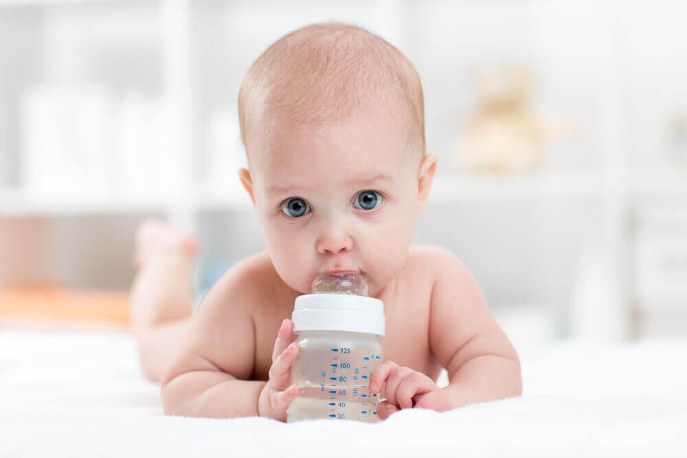A baby drinking water from a bottle.