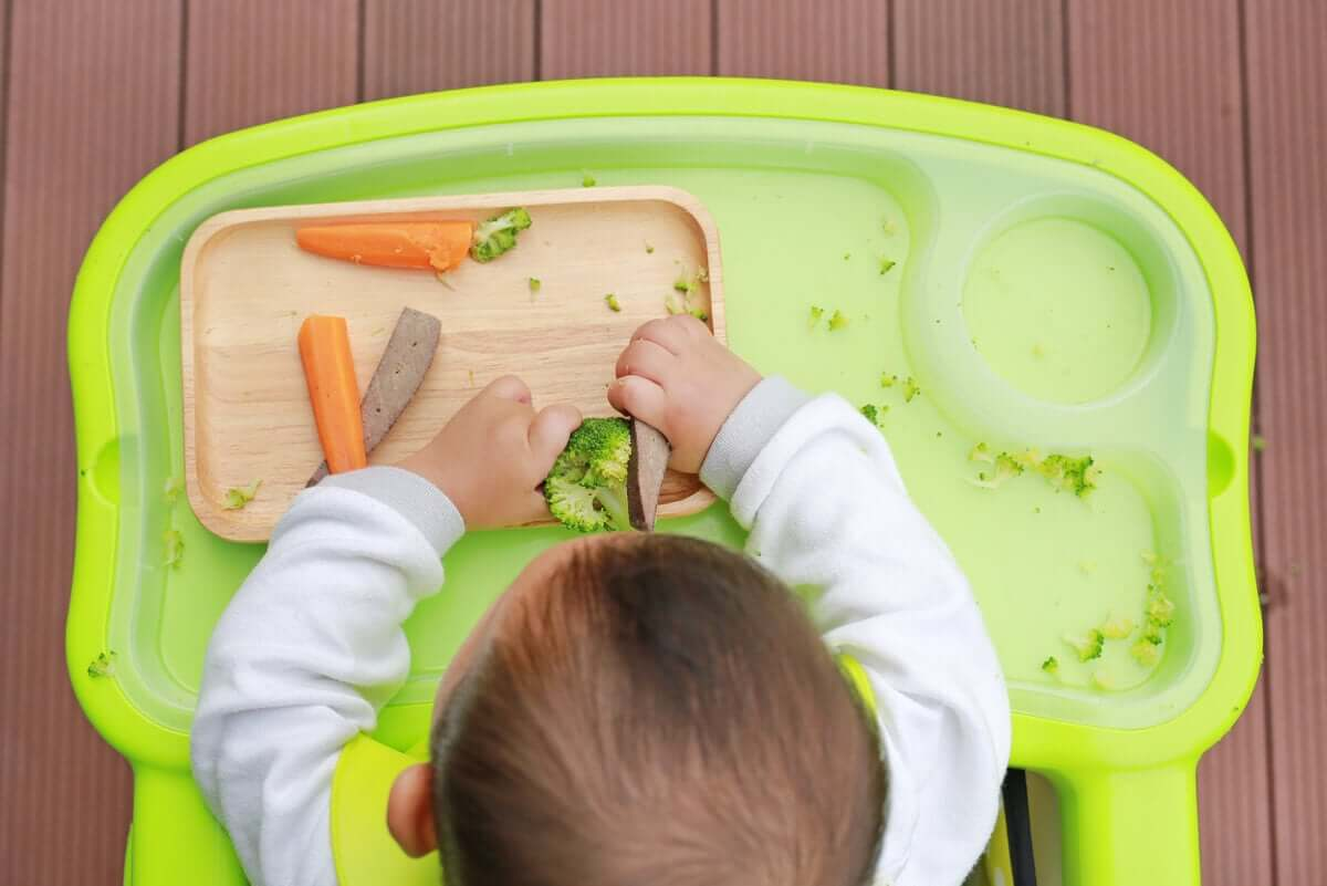 A baby eating vegetables.
